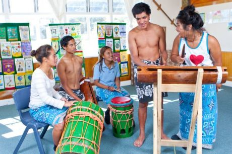 Image of Pacific Island students in costume, playing instruments in a classroom.